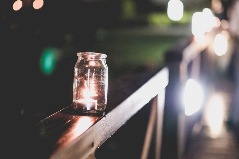Burning tea light candle on railing at night