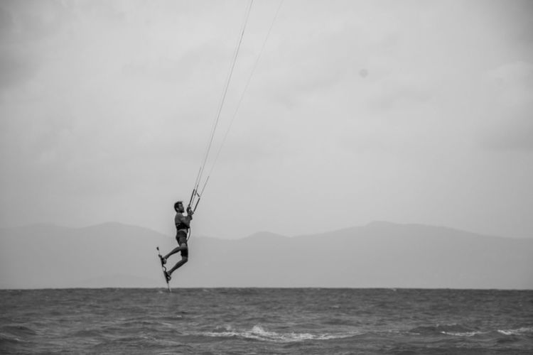 Young man kiteboarding over sea