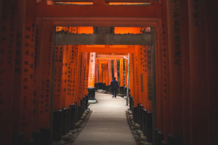 Rear view of man walking in corridor of temple