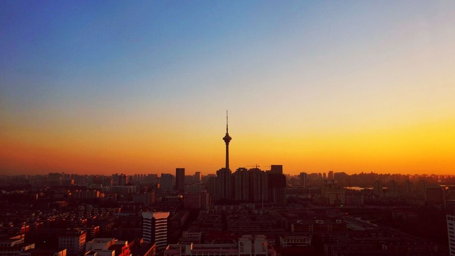 Silhouette tianjin radio and television tower in city against orange sky