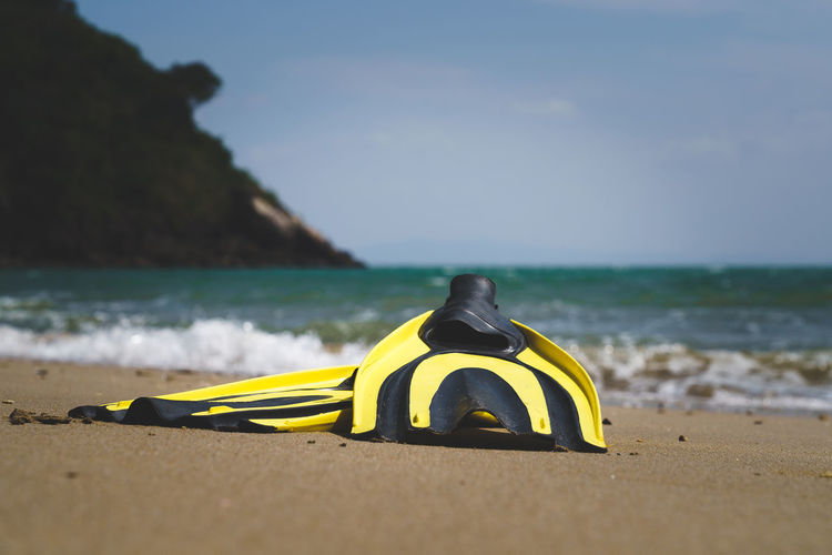 Yellow scuba fins on beach against water