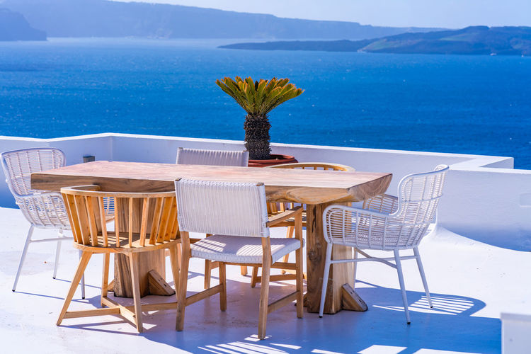 Chairs and table arranged against sea
