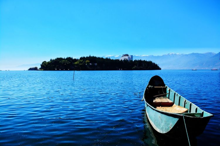 Boat in sea against clear blue sky