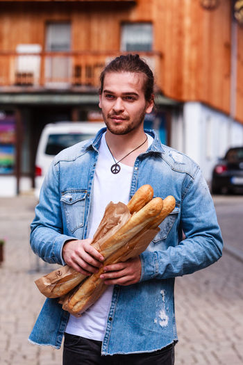 Young man comes from the baker and has French baguette in his hand. Baguette Breakfast Adult Bread Building Exterior Casual Clothing City Day Denim Jacket Food Food And Drink Freshness Front View Holding Human Hand Lifestyles Male Men One Person Outdoors People Real People Street Walking Young Adult