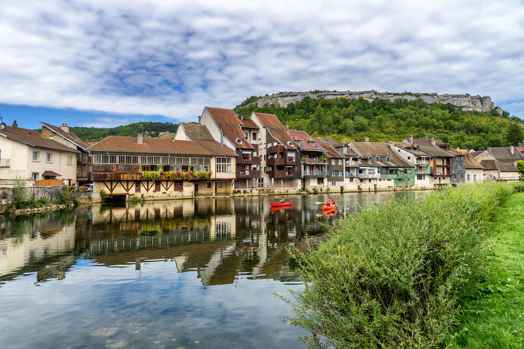 Paddlers in front of the typical houses on riverbanks in Ornans, France France Architecture Beauty In Nature Building Exterior Built Structure Cloud - Sky Day House Lake Nature Ornans Outdoors Paddling Reflection River Riverbank Sky Stilt House Tree Vacation Water Waterfront