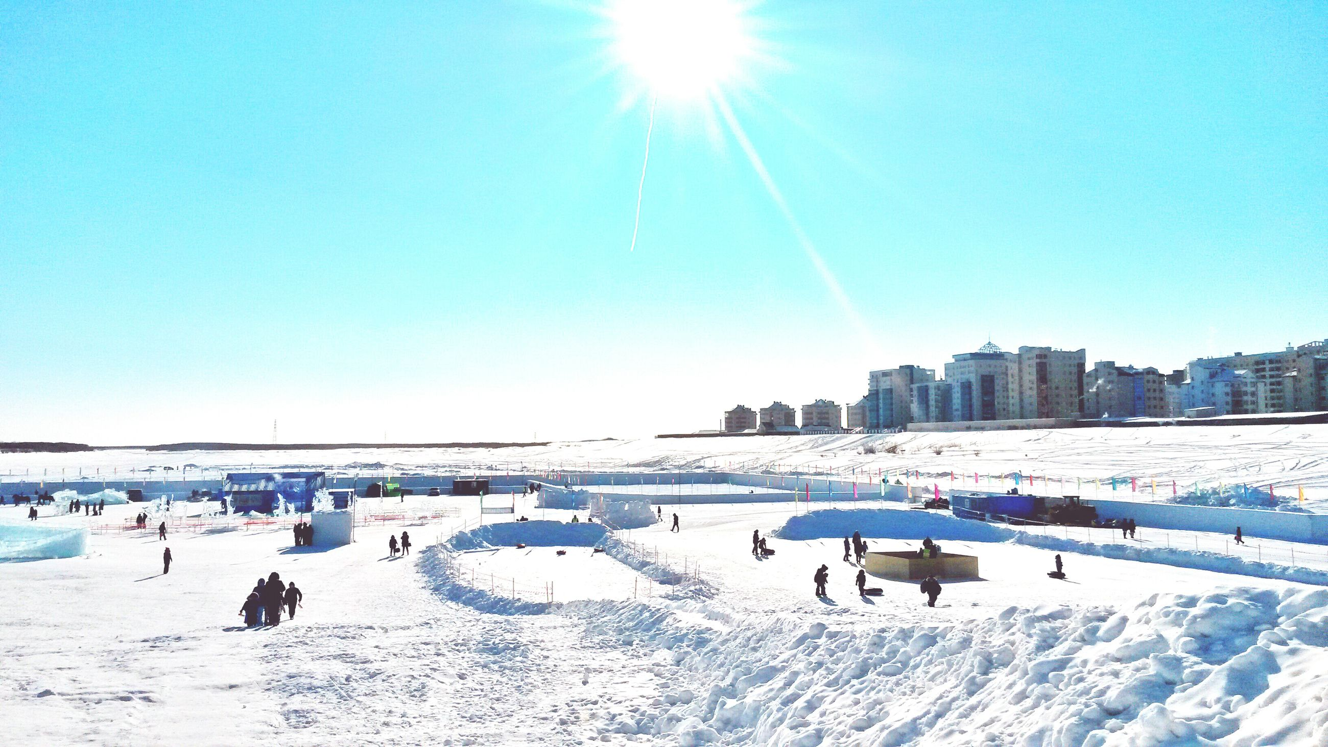 snow, winter, cold temperature, clear sky, season, blue, leisure activity, sunlight, large group of people, sun, lifestyles, men, built structure, vacations, copy space, covering, architecture, tourist, frozen