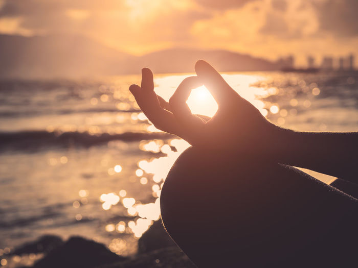 Yoga concept. Closeup woman hand practicing lotus pose on the beach at sunset Active Beach Beauty Body Part Exercise Fitness Hand Harmony Health Healthy Meditation Mind  Morning Outdoors Peace People Practice Relax Sea Summer Sunset Sunrise Woman Yoga Lifestyle
