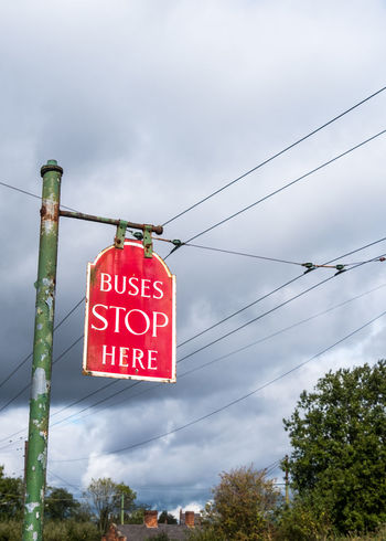 Red 'Buses Stop Here' sign at the Black Country Museum. BCLM Black Country Museum Power Lines Retro Sign Tram Tram Power Lines Tram Stop Transportation Black Country Living Museum Bus Stop Communication Day Electrified Hanging Low Angle View No People Power Cable Railway Red Road Sign Signpost Sky Text Tram Lines Tree