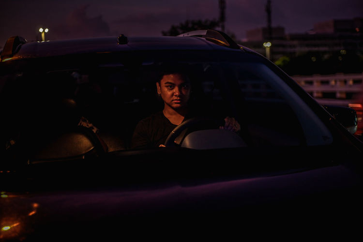 Portrait of man sitting in car at night