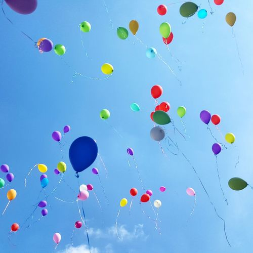 Low Angle View Of Colorful Helium Balloons Moving Up In Sky