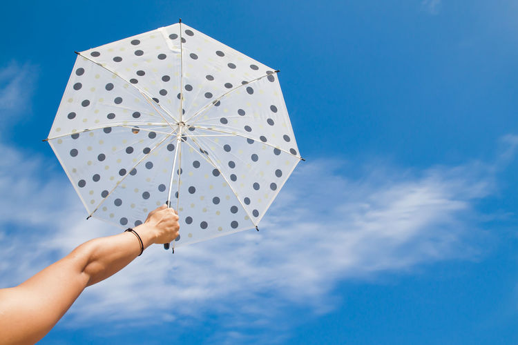 Low angle cropped hand of woman holding umbrella against blue sky