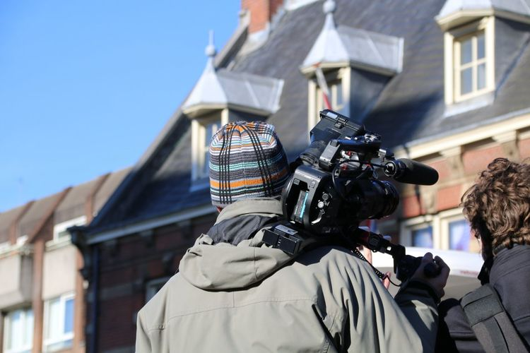 Men on built structure against sky