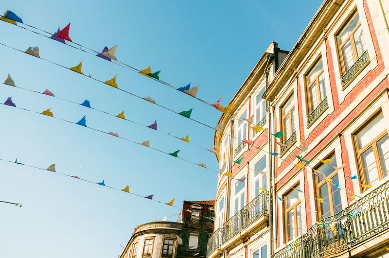 Low angle view of colorful buntings by building against clear sky