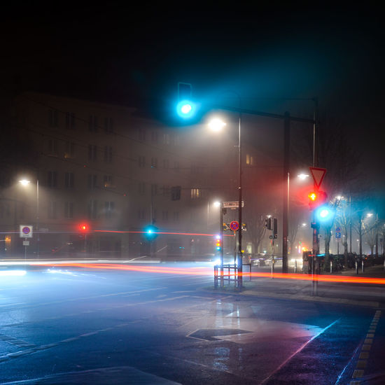Iwantthatcamera Bladerunner Berlin Foggy Weather Reflection Weather Architecture Building Exterior City Fog Foggy Illuminated Neon Neon Lights Night No People Outdoors Road Sign Stoplight Street Street Light Traffic Lights Trail Lights Transportation Fresh On Market 2018 10 HUAWEI Photo Award: After Dark