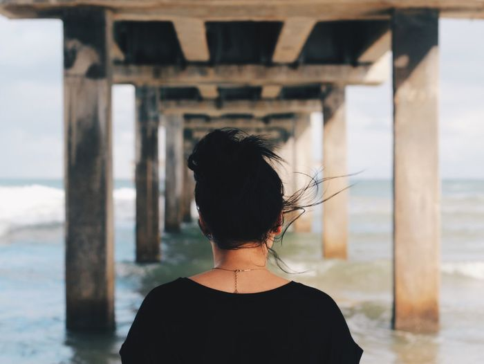 Rear View Of Woman Under Pier