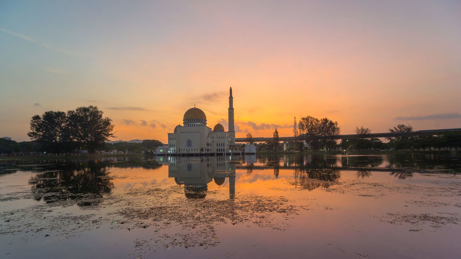 Reflection Architecture Building Exterior Built Structure Dome Mosque Nature No People Outdoors Place Of Worship Reflection Religion Sky Spirituality Sunset Travel Destinations Tree Water Waterfront