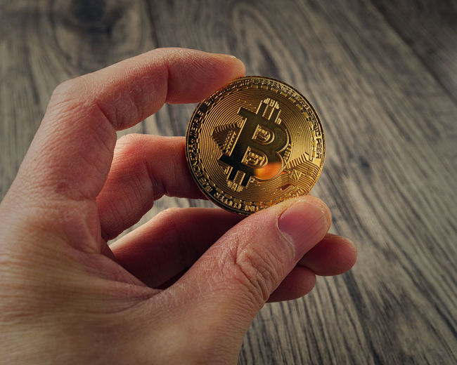 Cropped hand of woman holding bitcoin over table