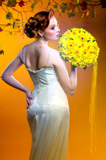 Rear View Of Bride Holding Bouquet While Standing Against Orange Background