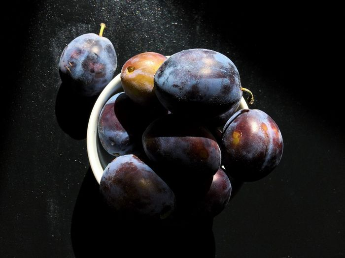 High Angle View Of Plums Fruit Close-up Group Of Objects Studio Shot Freshness Vibrant Color Large Group Of Objects No People Black Background Plum Indoors  Food Still Life Ready-to-eat Photography Color Image Food And Drink Black Background Freshness Overhead View Healthy Eating Horizontal