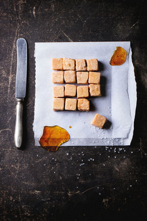 Fudge candy and caramel on baking paper, served with vintage knife over dark background. Top view Baking Paper Beige Brown Butterscotch Candy Caramel Comfort Food Confection Confectionery Creamy Cubes Dark Background Dark Photography Dessert Food Food And Drink Fudge Homemade Food Knife Square Sugar Sweet Food Toffee Top View Of Food Vintage