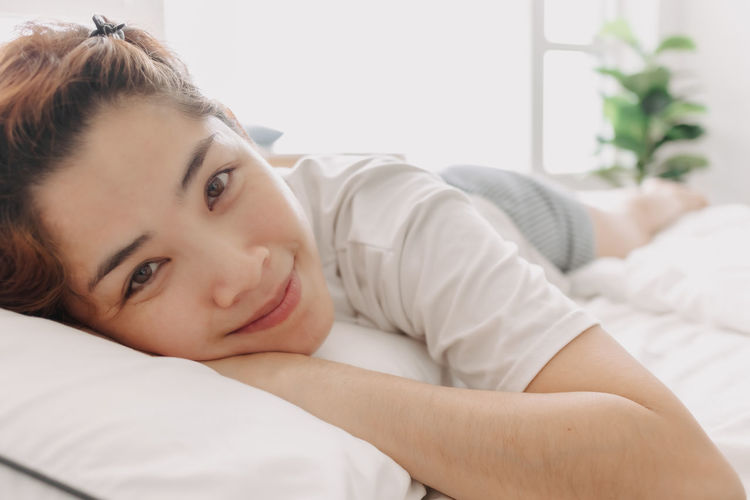 Portrait of young woman lying on bed at home