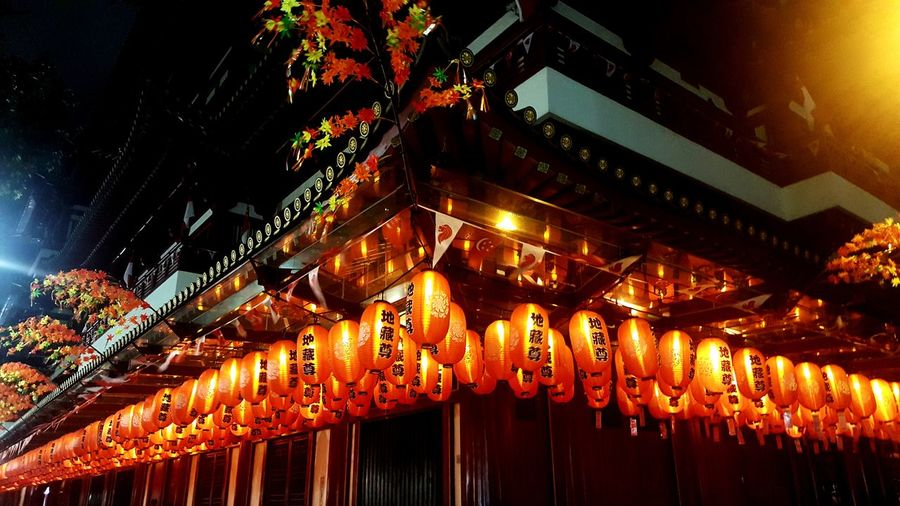 Low angle view of illuminated lanterns hanging by building at night
