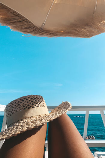 Midsection of woman with hat relaxing on yacht against sky