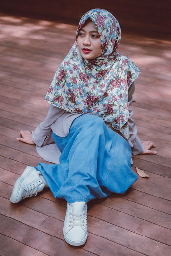 Low angle view of girl sitting on wooden floor