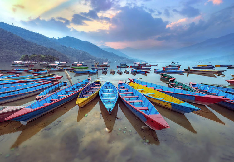 Color boat symbol of Phewa lake shore in Pokhara, Nepal. Phewa Lake Pokhara! Pokhara, Nepal Beauty In Nature Cloud - Sky Day Flag In A Row Moored Mountain Mountain Range Multi Colored Nature Nautical Vessel No People Outdoors Scenics Sea Sky Tranquility Water