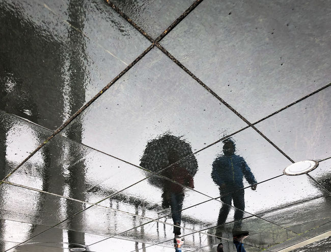 Real People Wet Water Rain Umbrella Men Walking Nature Day Lifestyles People High Angle View Full Length Reflection City Rainy Season Outdoors Paving Stone Reflections In The Water Reflection Reflection_collection
