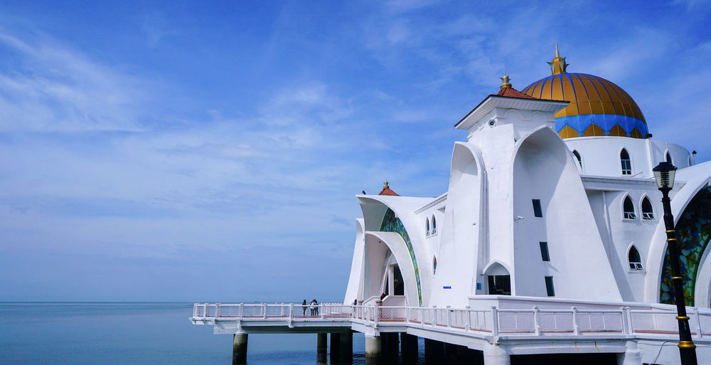 Traditional building by sea against sky