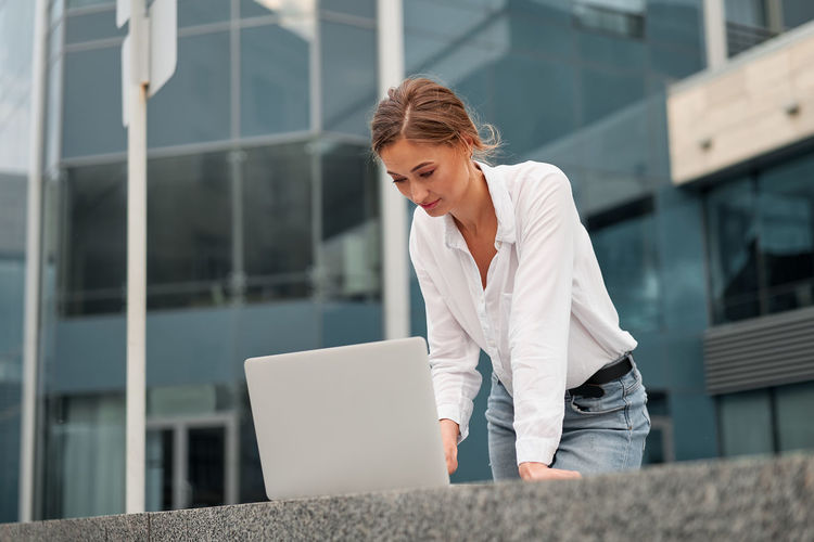 Close-up of smiling businesswoman using laptop standing outdoors