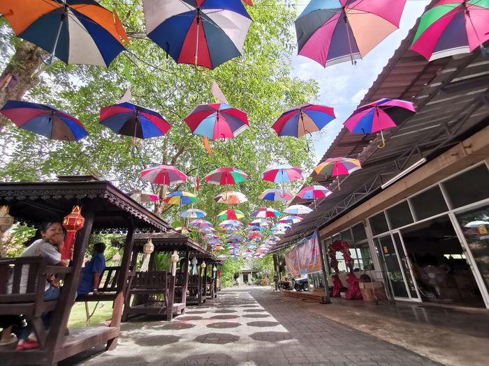 Multi colored umbrellas hanging amidst buildings in city