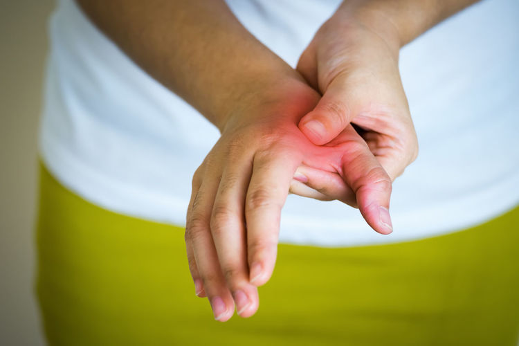 Midsection of woman suffering from pain on hand