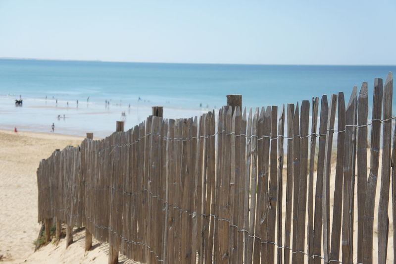 Beach Beauty In Nature Day Fence Groyne Horizon Over Water In A Row Incidental People Large Group Of Objects Nature Non-urban Scene Outdoors Protection Safety Scenics Sea Shore Sky Tourism Tranquil Scene Tranquility Travel Destinations Water Wood - Material Wooden Post