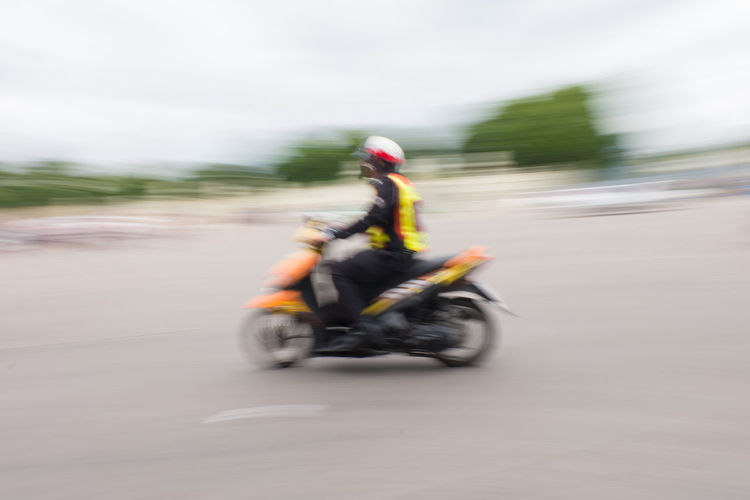 Blurred motion of man riding motorcycle on road