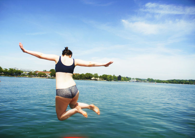 Arms Outstretched Arms Raised Beauty In Nature Bikini Blue Day Energetic Full Length Happiness Jumping Leisure Activity Mid-air Nature One Person One Woman Only Outdoors People Real People Sea Sky Summer Swimming Water Young Adult Young Women