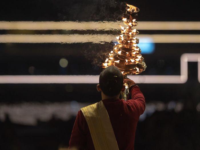 Rear view of hindu priest praying river at night
