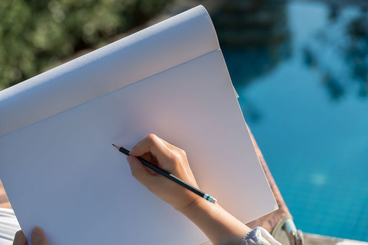 Hand sketching on drawing book. Woman hands holding note pad writing with black pencil relaxing by the pool at sunset ,water blurred background. Hands Woman Designer  Drawing Drawing Book Fashion Designing Pencil Drawing Relaxation Sketching Swimming Pool Water Reflection