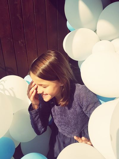 Smiling Girl With Eyes Closed Amidst Balloons