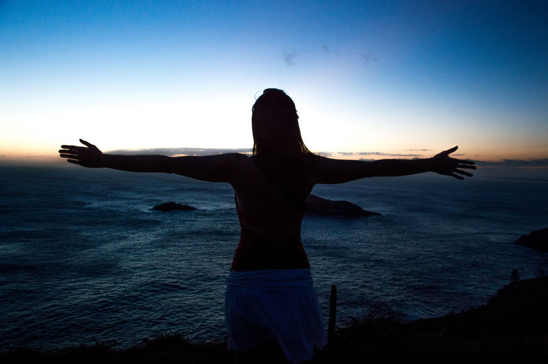 Woman with arms outstretched standing by sea against sky during sunset