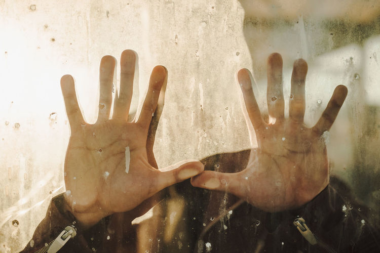 Close-up of hands on glass