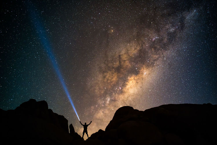 Low Angle View Of Silhouette Man Standing On Mountain Against Star Field