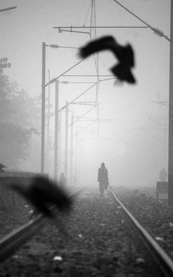 Silhouette man on railroad track against sky