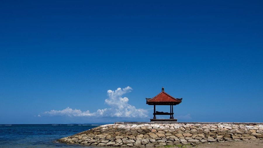 Gazebo by sea against blue sky