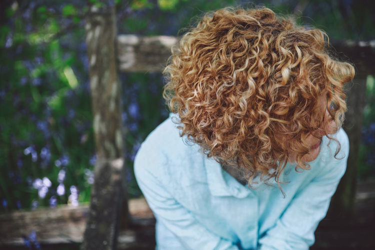 Close-up of woman with curly short hair sitting on bench