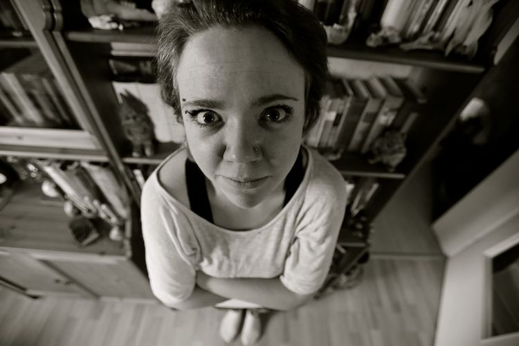 Close-up portrait of woman standing by bookshelf