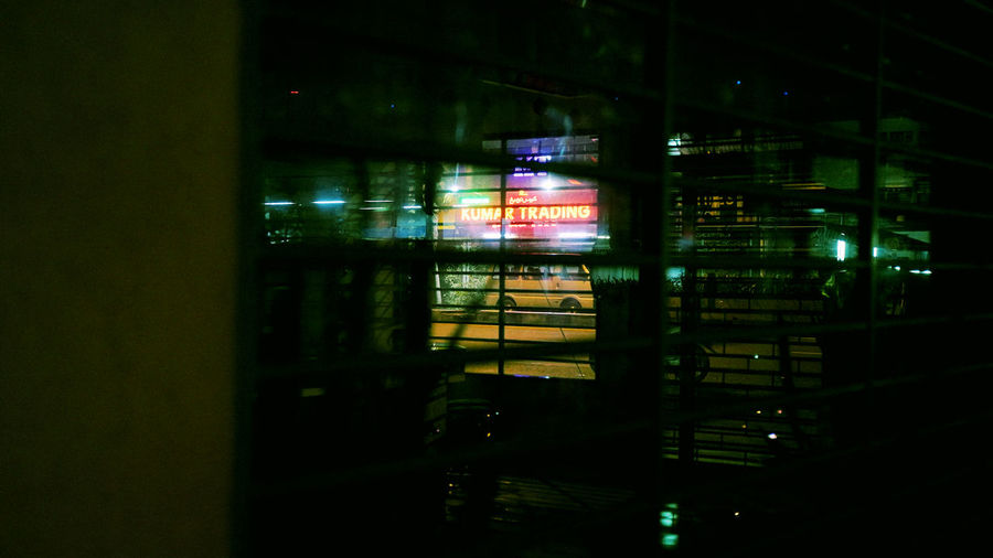 Illuminated building seen through glass window at night