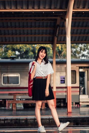 Portrait of smiling woman standing at railroad station platform