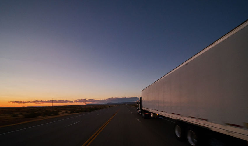 Transportation Sky Road Sunset Land Vehicle Mode Of Transportation The Way Forward Direction Nature Freight Transportation Truck Copy Space No People Clear Sky Semi-truck Diminishing Perspective Motor Vehicle vanishing point Outdoors Beauty In Nature Trucking